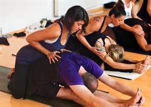 Bon professeur de Yoga ajustant un élève débutant