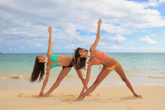 Posture du triangle en duo à la plage sans tapis de Yoga